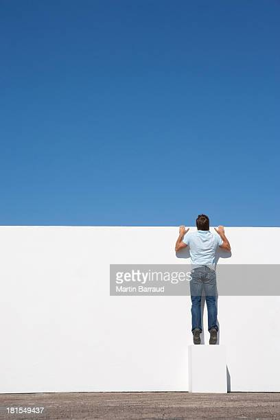 man peering over wall outdoors with blue sky - curiosity stock photos and pictures