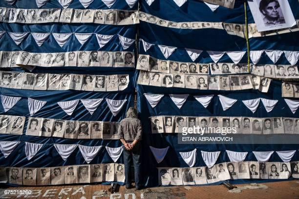 TOPSHOT A man peers behind portraits of victims of forced disappearance in the Plaza de Mayo square in Buenos Aires Argentina on April 30 during...
