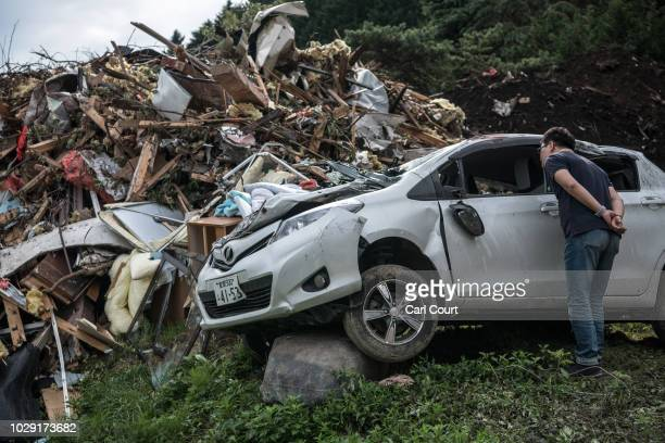 A man peers inside a destroyed car next to the ruins of a house that was struck by a landslide triggered by an earthquake on September 8 2018 in...