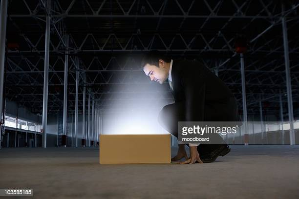 Man peers into yellow box shining bright light