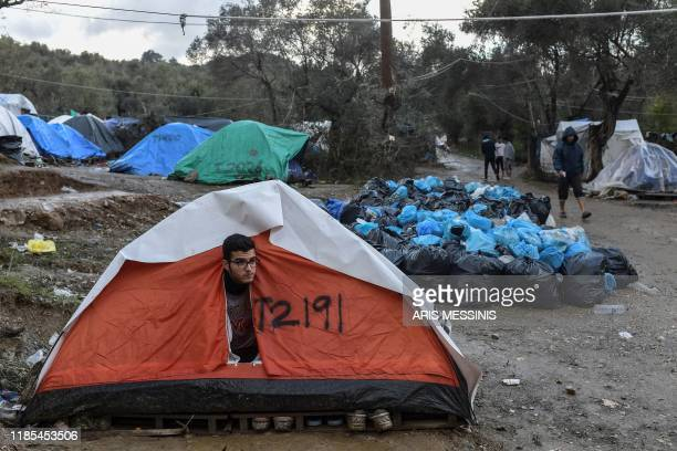 Man peers outside his tent at the makeshift camp next to the overcrowded refugee camp of Moria near the capital Mytilene in the island of Lesbos on...