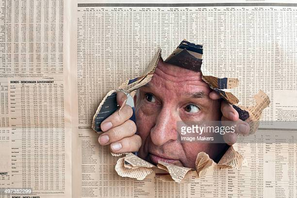man peers through hole in financial paper