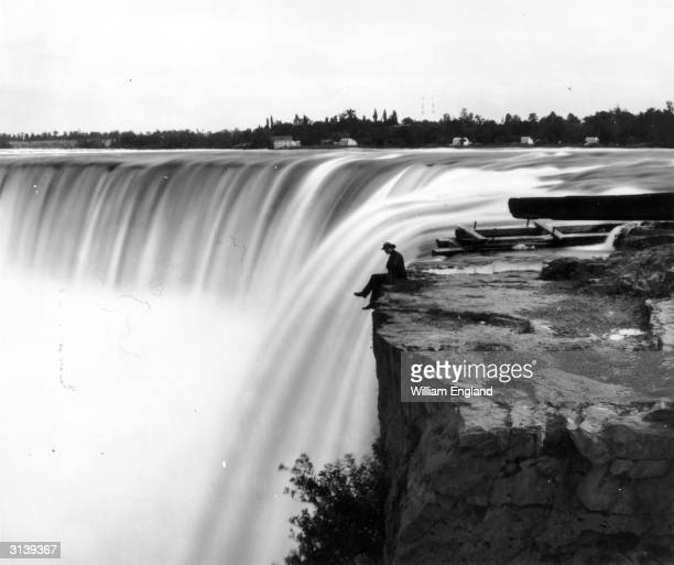 Man perches on Table Rock at the edge of the Horseshoe Falls, the crescent-shaped cataract on the Canadian side of Niagara Falls.
