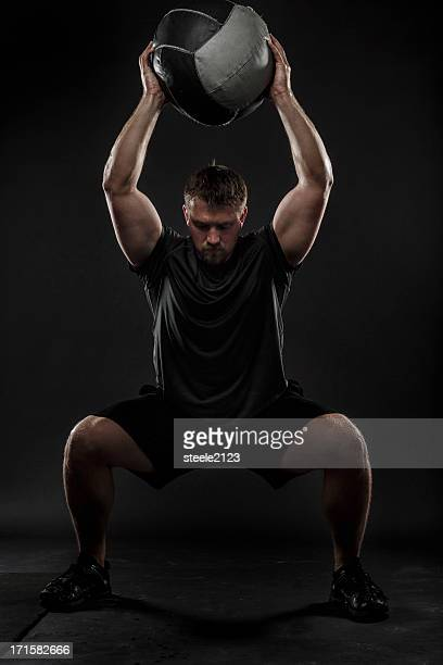 a man performing a medicine ball squat - medicine ball stock pictures, royalty-free photos & images