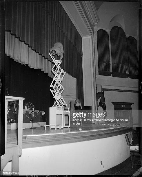 Man performing balancing act with piano and folding chairs with Walt Harper band playing in background and woman in leotard observing on stage in...
