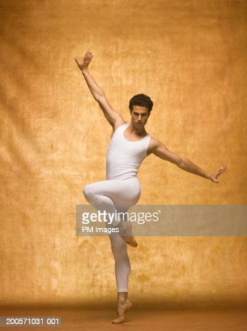 man performing ballet pose with arms outstretched highres