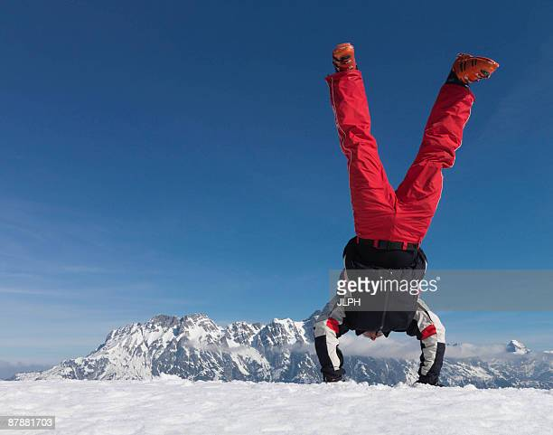 man performing handstand on mountain - ski humour photos et images de collection