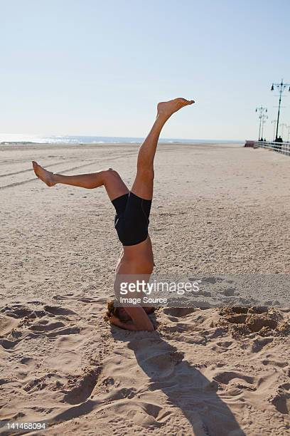 man performing headstand on a beach - only mature men stock pictures, royalty-free photos & images