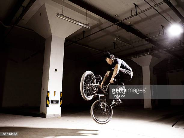 man performing jump on bmx bike - bmx cycling stock pictures, royalty-free photos & images