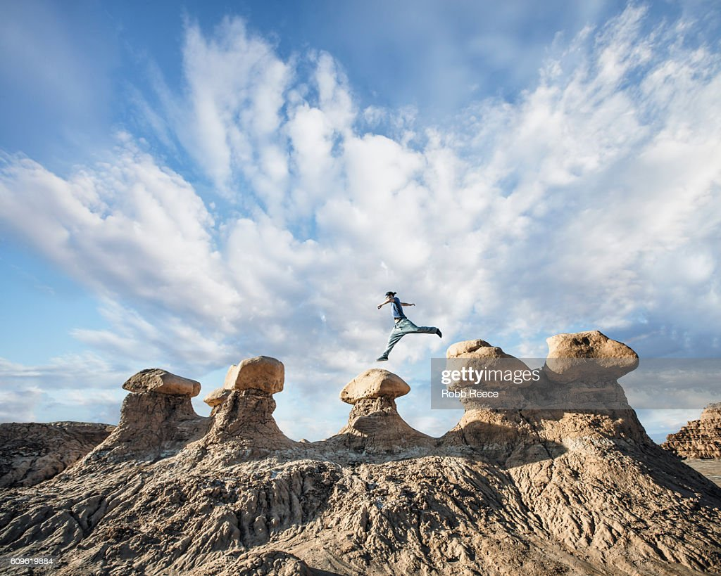 A man performing parkour outdoors on rock formations in the desert : Stock Photo