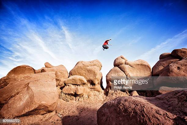 a man performing parkour outdoors on rock formations in the desert - robb reece stock photos and pictures