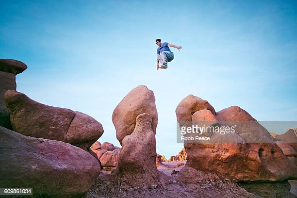 a man performing parkour outdoors on rock formations in the desert - robb reece stock pictures, royalty-free photos & images