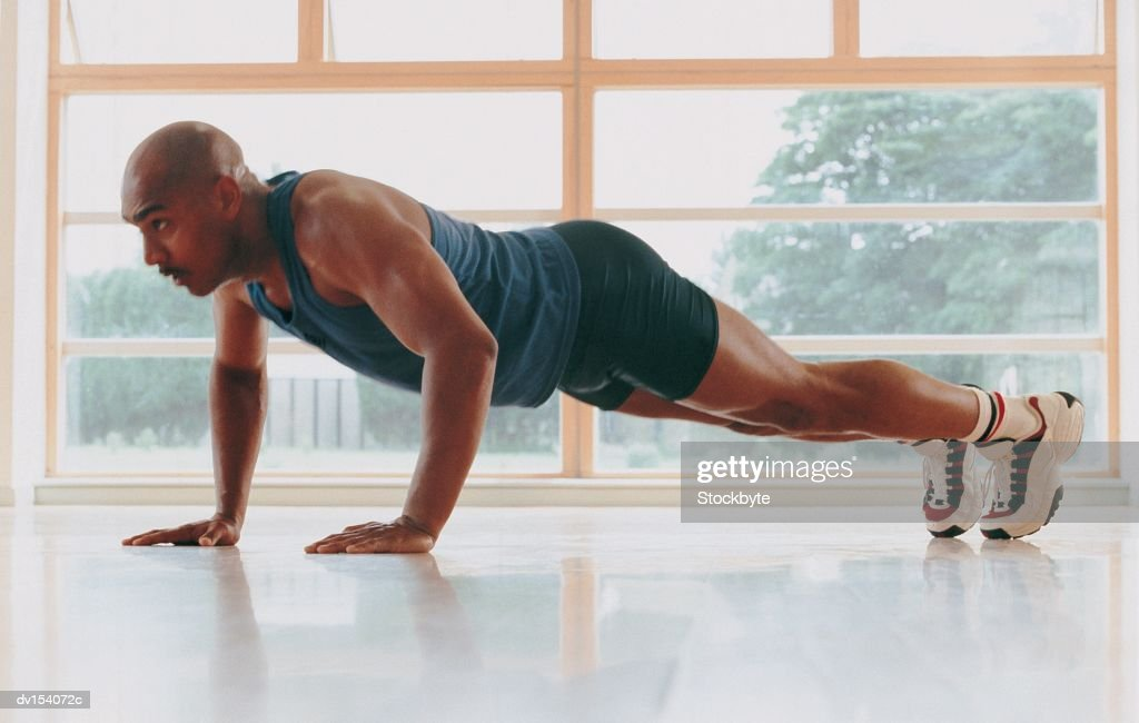 Man performing push-ups : Stock Photo