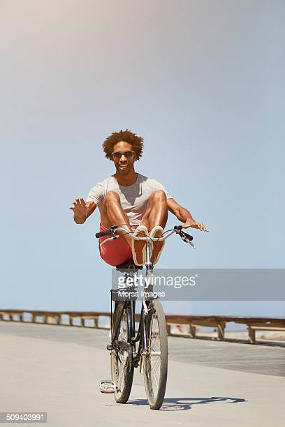 Man performing stunt on bicycle against blue sky
