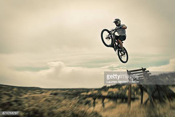 man performing stunt on bicycle against sky - bmx cycling stock pictures, royalty-free photos & images