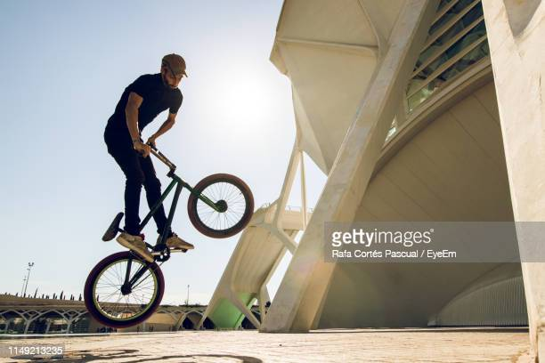 man performing stunt on bicycle in city - bmx cycling stock pictures, royalty-free photos & images