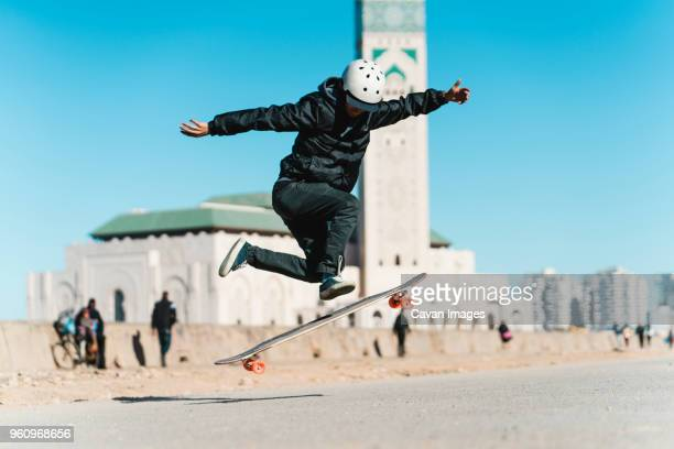 Man performing stunt while skateboarding against Mosque Hassan II