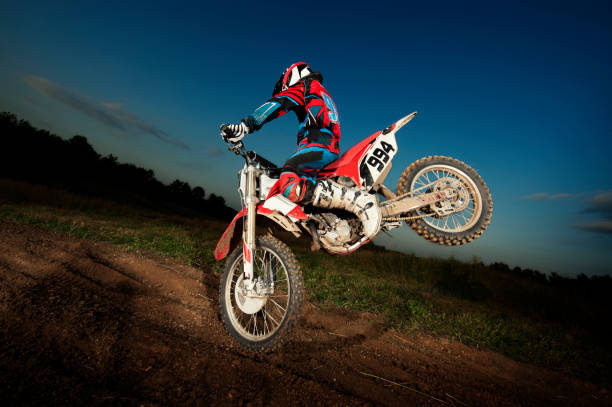 Man performing stunt with dirt bike on field at dusk