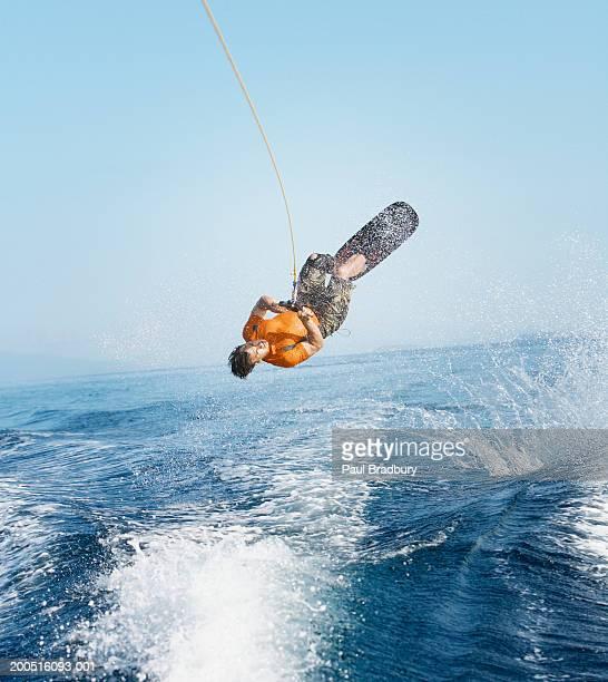 Man performing wakeboarding stunt at sea