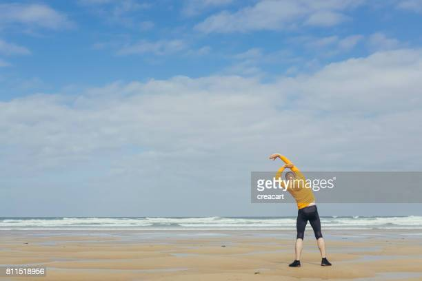 Man performing warm up exercises before moving beach run.