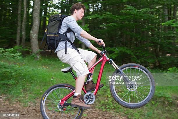 Man performing wheelie on mountain bike