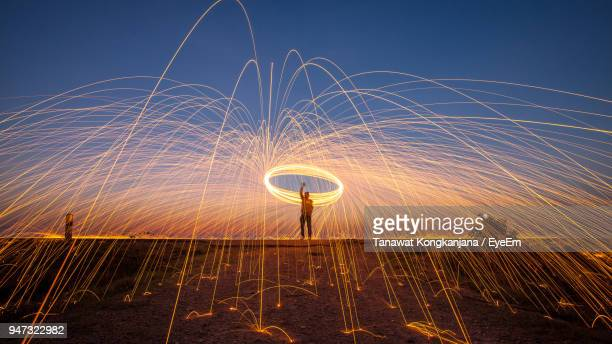 man performing with wire wool against sky during sunset - lichtmalerei stock-fotos und bilder