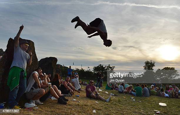 Man performs a back flip at the stone circle during the Glastonbury Festival at Worthy Farm, Pilton on June 25, 2015 in Glastonbury, England.