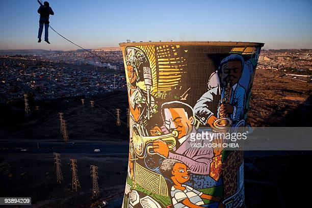 Man performs a bungee jump from the top of a thermal power planted, closed 11 years ago, in Soweto on June 28, 2009. The cooling tower is about 100m...