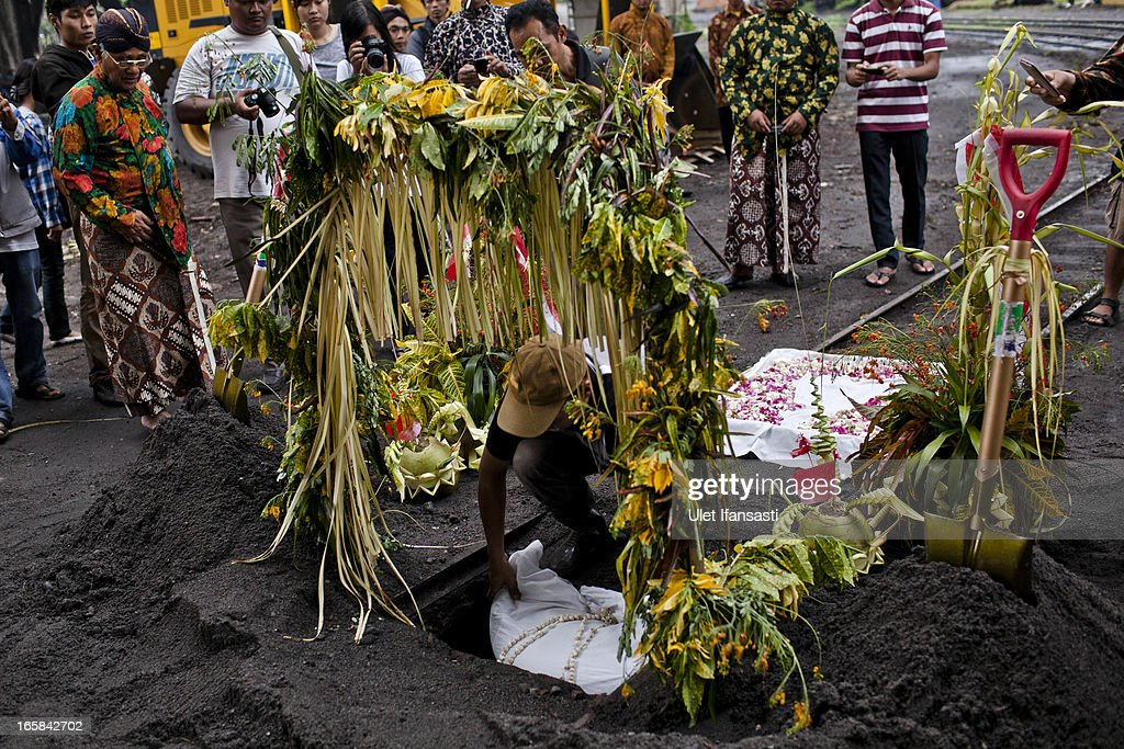 A man performs a ritual as he buries a buffalo head as an offering during the Cembengan ritual 'Manten Tebu' at Madukismo sugar cane factory on April 6, 2013 in Yogyakarta, Indonesia. The Cembengan ritual, performed to bring about a good season's sugarcane crop, is held annually before the milling and processing season starts in Indonesian sugar mills.
