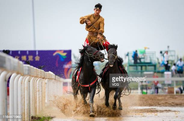 Man performs horse riding skills during the 6th Inner Mongolia International Equestrian Festival on July 27, 2019 in Hohhot, Inner Mongolia...