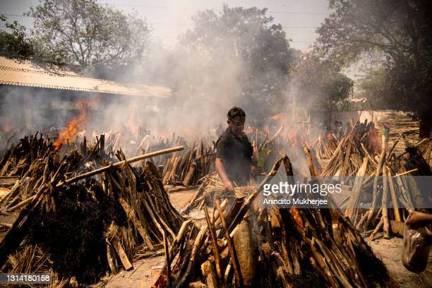 Man performs the last rites of his relative who died of the Covid-19 coronavirus disease as other funeral pyres are seen burning during a mass...