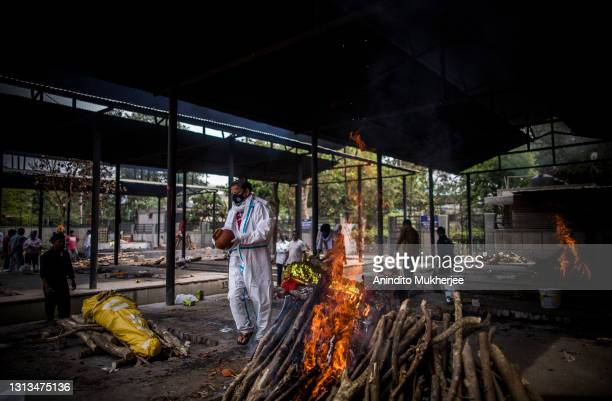 Man performs the last rites to his wife who died of the Covid-19 coronavirus disease during a mass cremation at a crematorium on April 20, 2021 in...