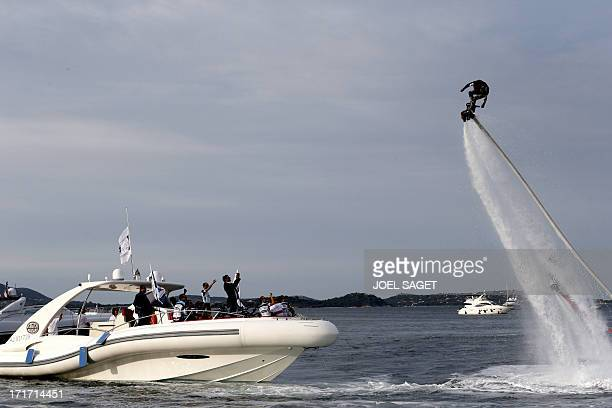 A man performs with a flyboard near the riders of Omega Pharma QuickStep team on a boat on June 27 2013 in PortoVecchio on the French island of...