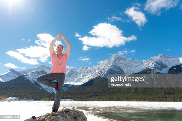 Man performs yoga moves on rock island, mountains