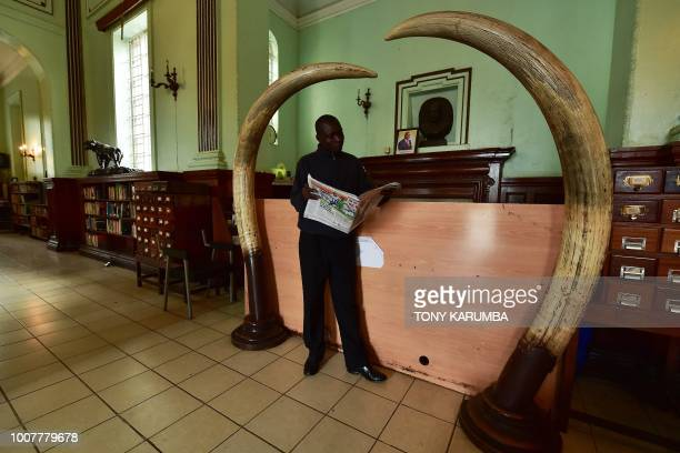 A man peruses a newspaper at the book checkout counter underneath giant elephant ivory tusks at the colonialera McMillan Memorial Library in the...