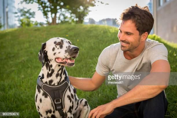 Man petting Dalmatian in a park