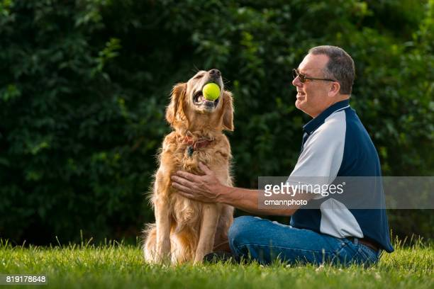 man petting his dog at sunset - cmannphoto stock pictures, royalty-free photos & images