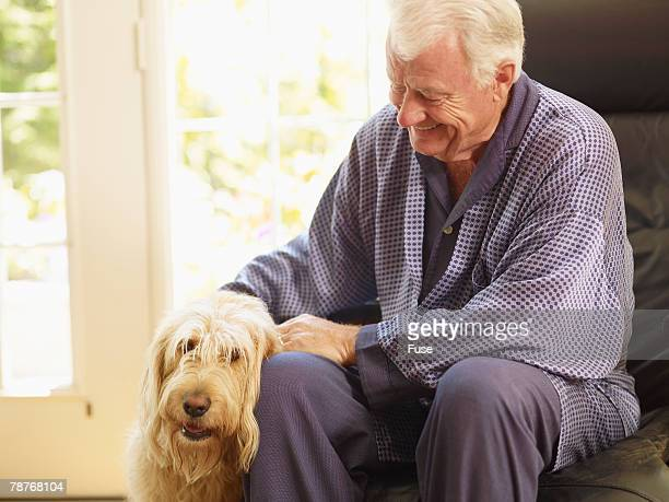 man petting pet dog - labradoodle stock photos and pictures