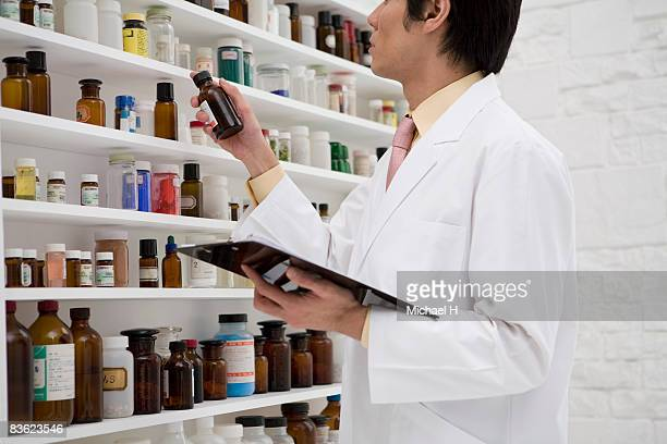Man pharmacist who chooses medicine from shelf