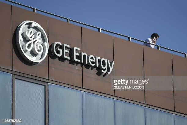 Man phones atop the building of US giant General Electric past the logo of the company in Belfort, eastern France, on September 17, 2019. - About a...