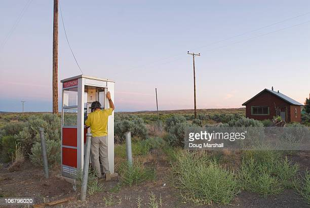 A man phones from a isolated phone booth.