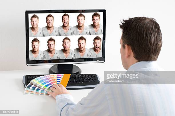 Man photo edits on computer with color swatch