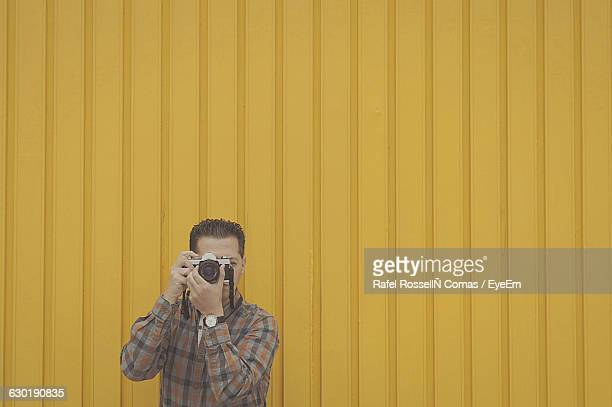 Man Photographing Against Yellow Wall