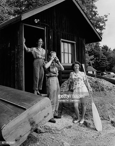 man photographing and women looking out while standing outside house - {{ contactusnotification.cta }} stockfoto's en -beelden