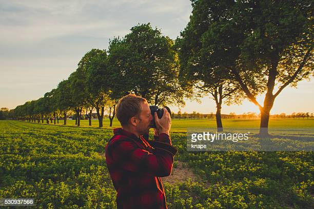 Mann Fotografieren während dem Sonnenuntergang in Natur