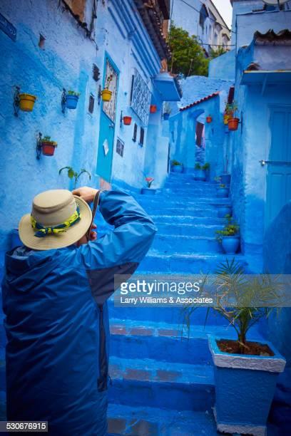 man photographing blue historical village steps, chefchaouen, chefchaouen, morocco - chefchaouen fotografías e imágenes de stock