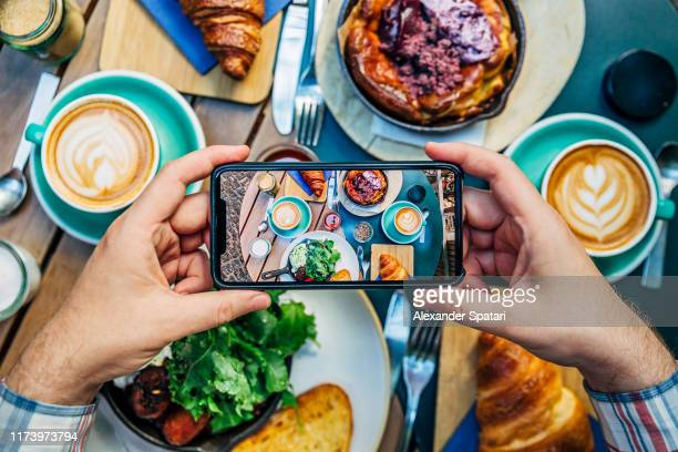 man photographing breakfast in a cafe with smartphone - kaffee getränk stock-fotos und bilder