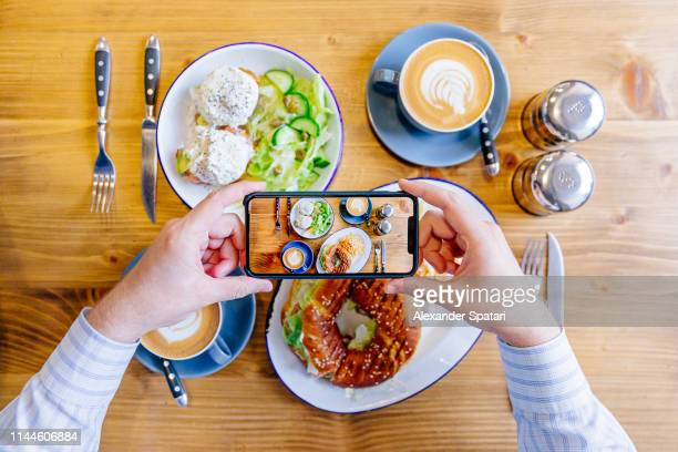 man photographing breakfast with smartphone, personal perspective point of view - healthy eating stock pictures, royalty-free photos & images