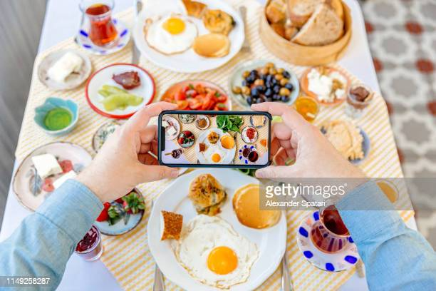 Man photographing breakfast with smartphone