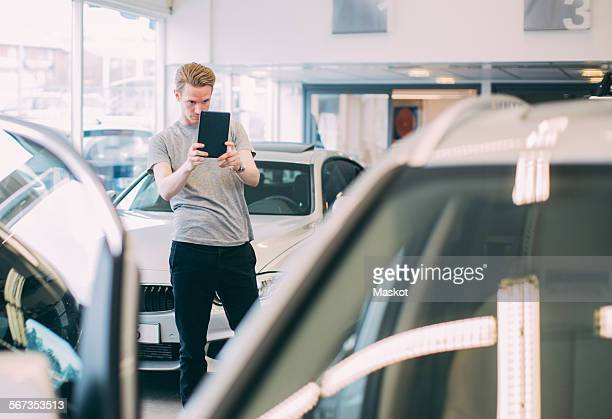 Man photographing car through digital tablet at dealership store